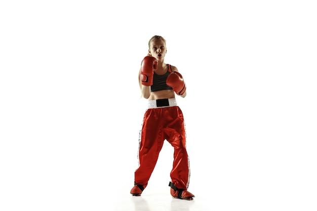 흰 벽에 고립 된 젊은 여성 킥복싱 전투기 훈련. 무술에서 연습하는 빨간 운동복에 백인 금발 소녀. 스포츠, 건강한 라이프 스타일, 모션, 액션, 청소년의 개념.