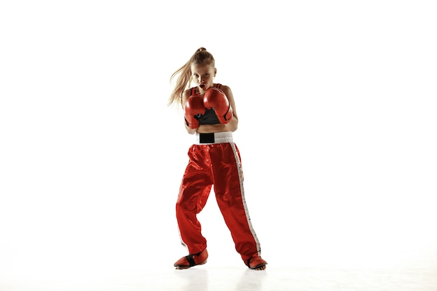 Young female kickboxing fighter training isolated on white background.