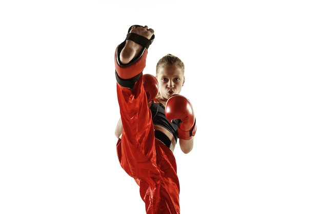Young female kickboxing fighter training isolated on white background