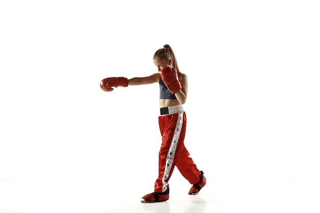 Young female kickboxing fighter training isolated on white wall. caucasian blonde girl in red sportswear practicing in martial arts. concept of sport, healthy lifestyle, motion, action, youth.