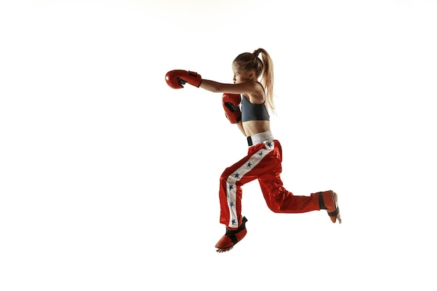 Young female kickboxing fighter training on white