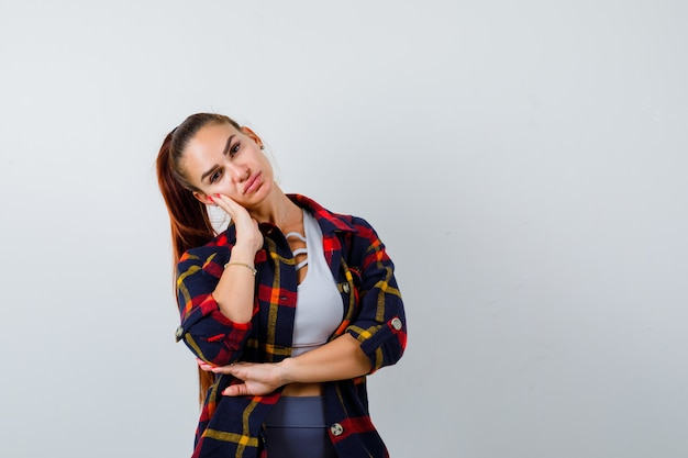 Young female leaning cheek on hand in crop top, checkered shirt, pants and looking thoughtful , front view.