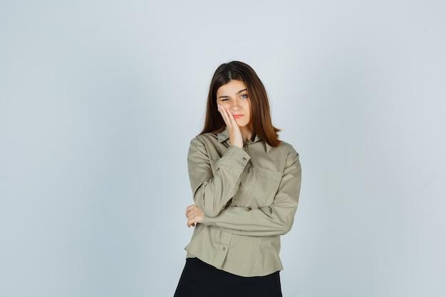Guancia pendente femminile giovane a portata di mano in camicia, gonna e guardando sconvolto. vista frontale.