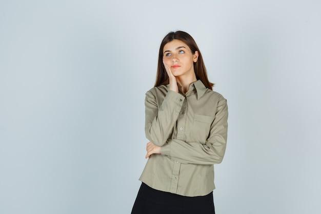 셔츠, 치마에 손에 뺨을 기대고 생각에 잠겨있는 찾고 젊은 여성, 전면보기.