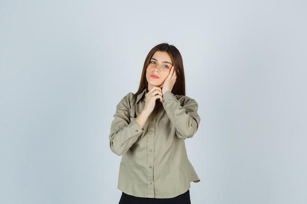 셔츠, 치마에 손바닥에 뺨을 기대고 생각에 잠겨있는 찾고 젊은 여성, 전면보기.