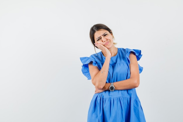 Giovane femmina guancia pendente sul palmo alzato in abito blu e dall'aspetto cupo