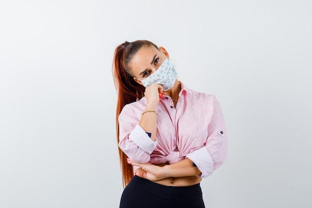 Giovane donna faccia pendente sul pugno in camicia, pantaloni, mascherina medica e guardando fiducioso. vista frontale.