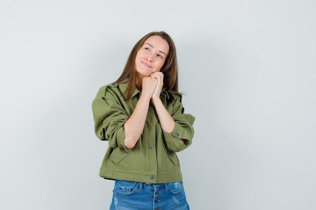ジャケット、ショートパンツ、キュートに見える、正面図で握りしめられた手に顔を傾ける若い女性。
