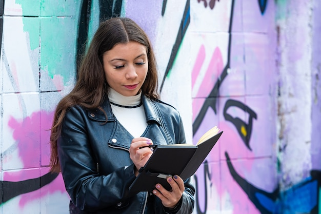 A young female leans against a wall sprayed with graffiti and makes notes in a black notebook