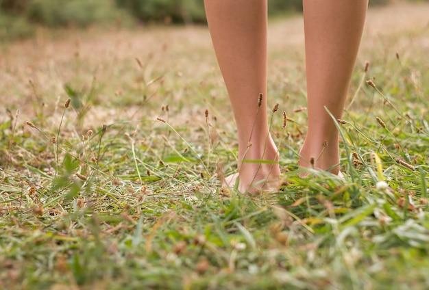 Молодые женские ножки, идущие по траве