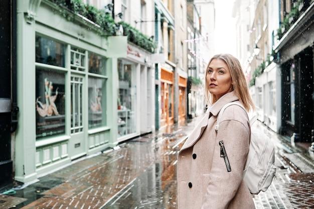 Блогер молодой женщины позирует на улице в центре лондона