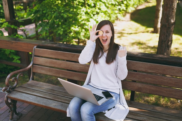 Young female in light casual clothes. woman sitting on bench holding bitcoin coin of golden color working on modern laptop pc computer in street outdoors. mobile office online virtual currency concept