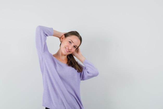Giovane donna in camicetta lilla in posa con le mani sulla testa e che sembra allegra