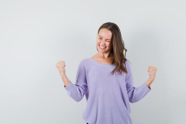 Giovane donna in camicetta lilla che mostra il gesto del vincitore e che sembra gioiosa