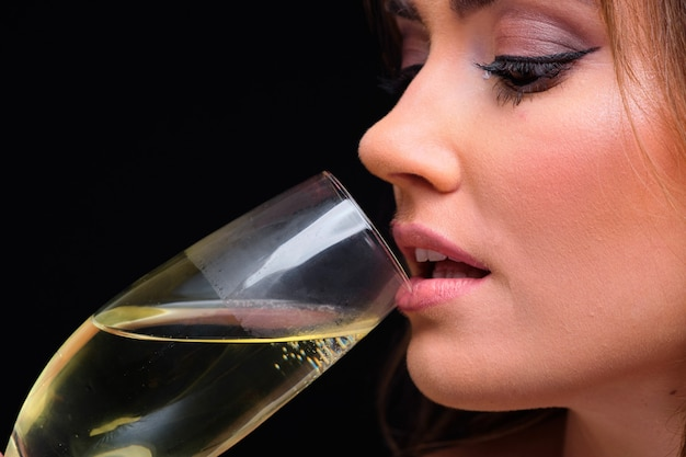 Of young female lips drinking champagne against black
