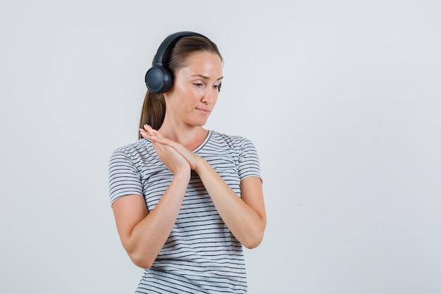 縞模様のtシャツの正面図でヘッドフォンで注意深く聞いている若い女性。