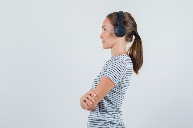 ストライプのtシャツのヘッドフォンで注意深く聞いている若い女性。