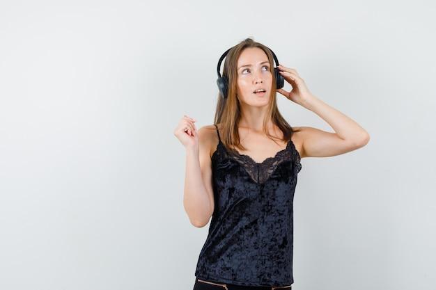 Молодая женщина слушает музыку в наушниках в черной майке