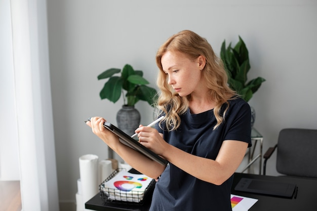 Young female logo designer working on a graphic tablet
