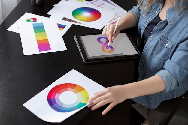 Молодой женский дизайнер логотипа, работающий над графическим планшетом