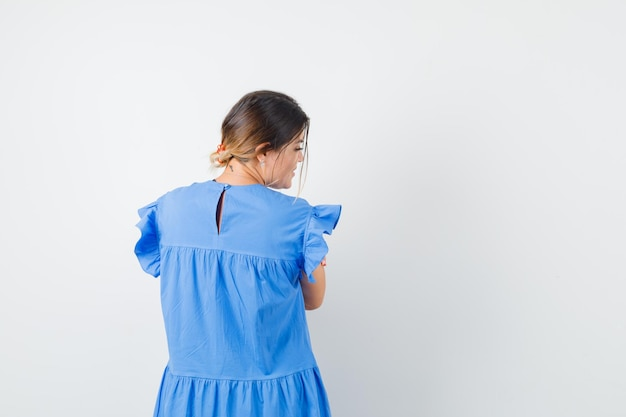 Молодая женщина смотрит в сторону в синем платье и выглядит очаровательно