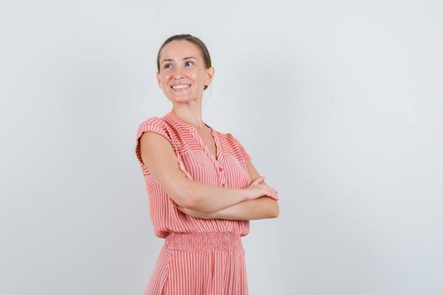 縞模様のドレスを着て腕を組んで脇を見て、陽気に見える若い女性、正面図。