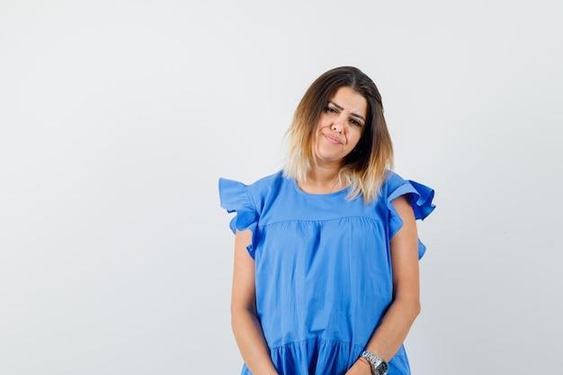 青いドレスを着てカメラを見て動揺している若い女性