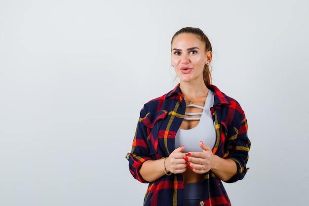 クロップトップ、市松模様のシャツ、パンツでカメラを見て、驚いて、正面図を見て若い女性。
