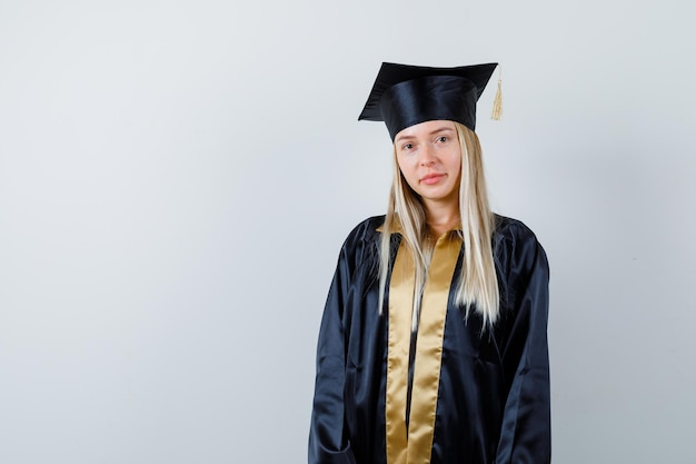 대학원 제복을 입은 카메라를보고 현명한 찾고 젊은 여성.