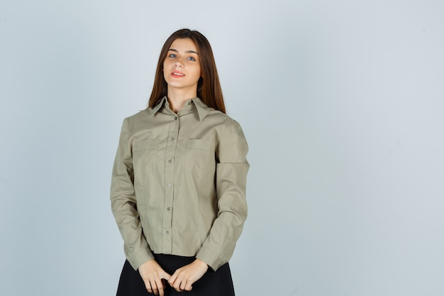 Молодая женщина смотрит в камеру в рубашке, юбке и выглядит веселой, вид спереди.