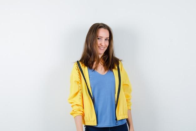 Молодая женщина смотрит в камеру в футболке, куртке и выглядит веселым, вид спереди.