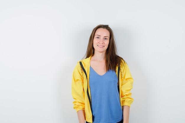 Молодая женщина смотрит в камеру в футболке, куртке и выглядит восхитительно, вид спереди.