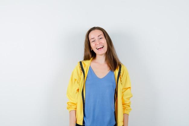Молодая женщина смотрит на камеру в футболке, куртке и выглядит счастливой. передний план.