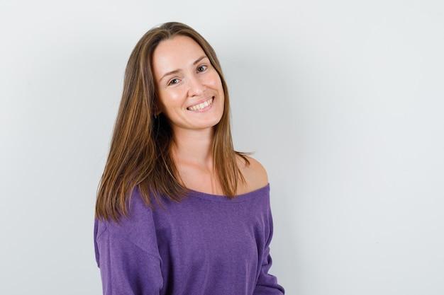 紫のシャツを着てカメラを見て、陽気に見える若い女性。正面図。