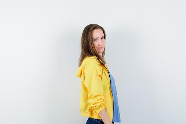 Tシャツ、ジャケットを着て肩越しにカメラを見て、楽しく見える若い女性。 。
