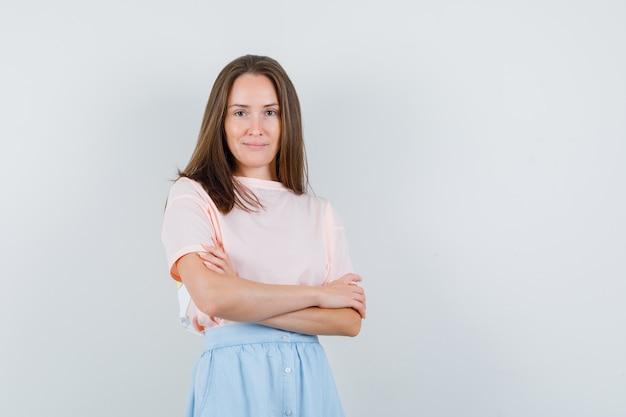 Молодая женщина, глядя на камеру со скрещенными руками в футболке, юбке, вид спереди.