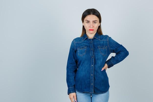 Молодая женщина смотрит вперед, держа руку на бедре в джинсовой рубашке и джинсах и выглядит обиженной