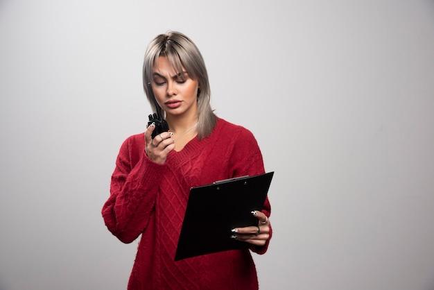 회색 배경에 라디오 송수신기를 보고 있는 젊은 여성.
