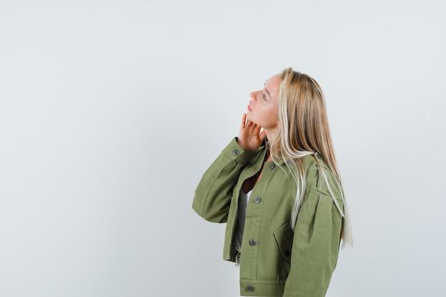 Молодая женщина смотрит в куртку, блузку и смотрит сосредоточенно. . свободное место для вашего текста