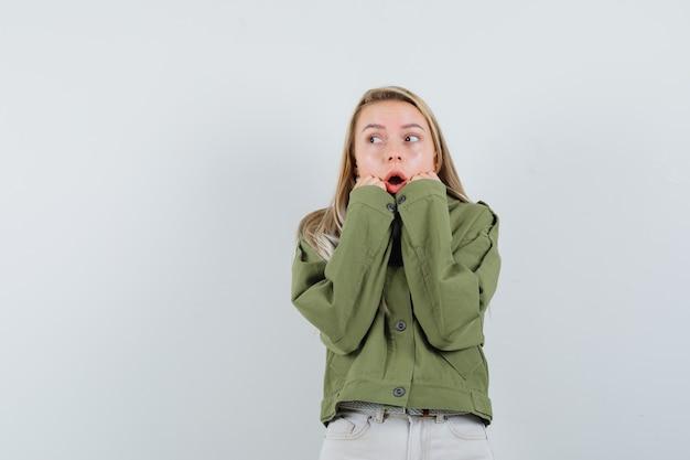 녹색 재킷, 청바지에 그녀의 턱에 손을 잡고 멀리보고 흥분 찾고 젊은 여성. 전면보기.