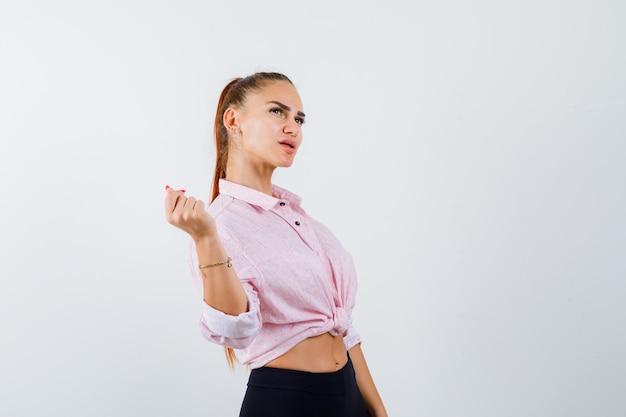 Молодая женщина смотрит в сторону, стоя в повседневной рубашке, штанах и уверенно глядя, вид спереди.