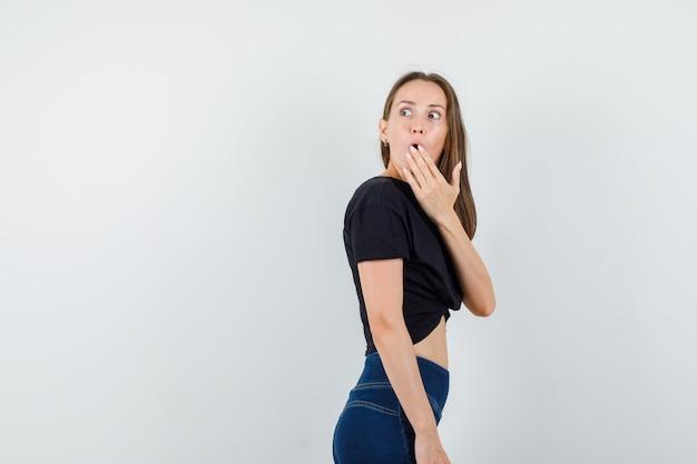 黒のブラウス、ズボンを着て、驚いたように口に手を当てて振り返る若い女性。