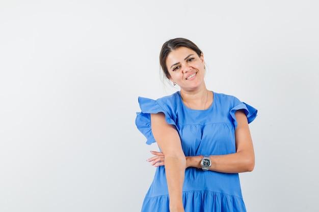 Giovane donna che guarda la telecamera in abito blu e sembra allegra