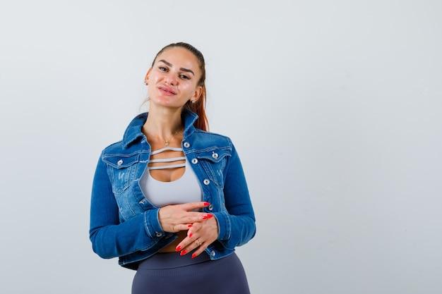 Giovane donna che guarda l'obbiettivo in crop top, giacca, pantaloni e sembra sicura. vista frontale.