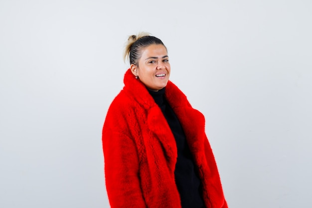 Young female looking at camera in sweater, red fur coat and looking happy , front view.
