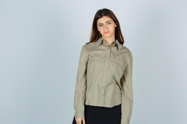 Giovane donna che guarda l'obbiettivo mentre il viso accigliato, le labbra curve in camicia, gonna e guardando giù. vista frontale.