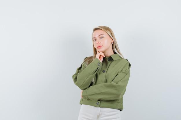 녹색 재킷, 청바지 전면보기에서 신중 하 게 찾고 젊은 여성.