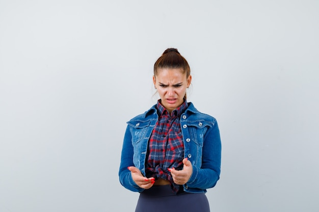 Giovane donna che guarda in basso in camicia a scacchi, giacca, pantaloni e sembra indecisa. vista frontale.