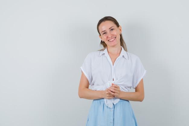 Giovane donna che guarda davanti in camicetta e gonna e sembra ottimista