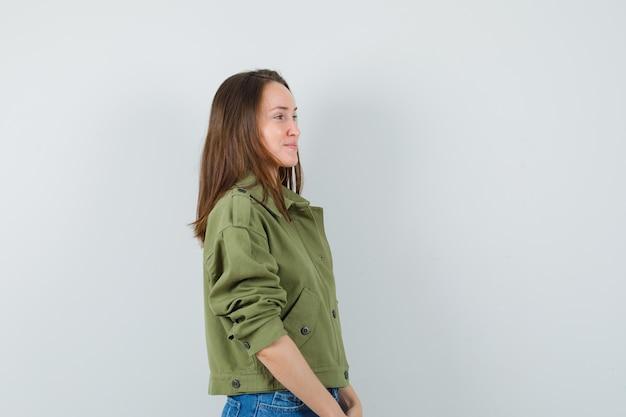 Giovane donna in cerca di fronte a lei in giacca, pantaloncini e un bell'aspetto.